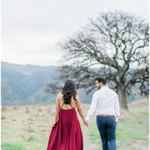couple walking hand in hand on a trail with oak trees