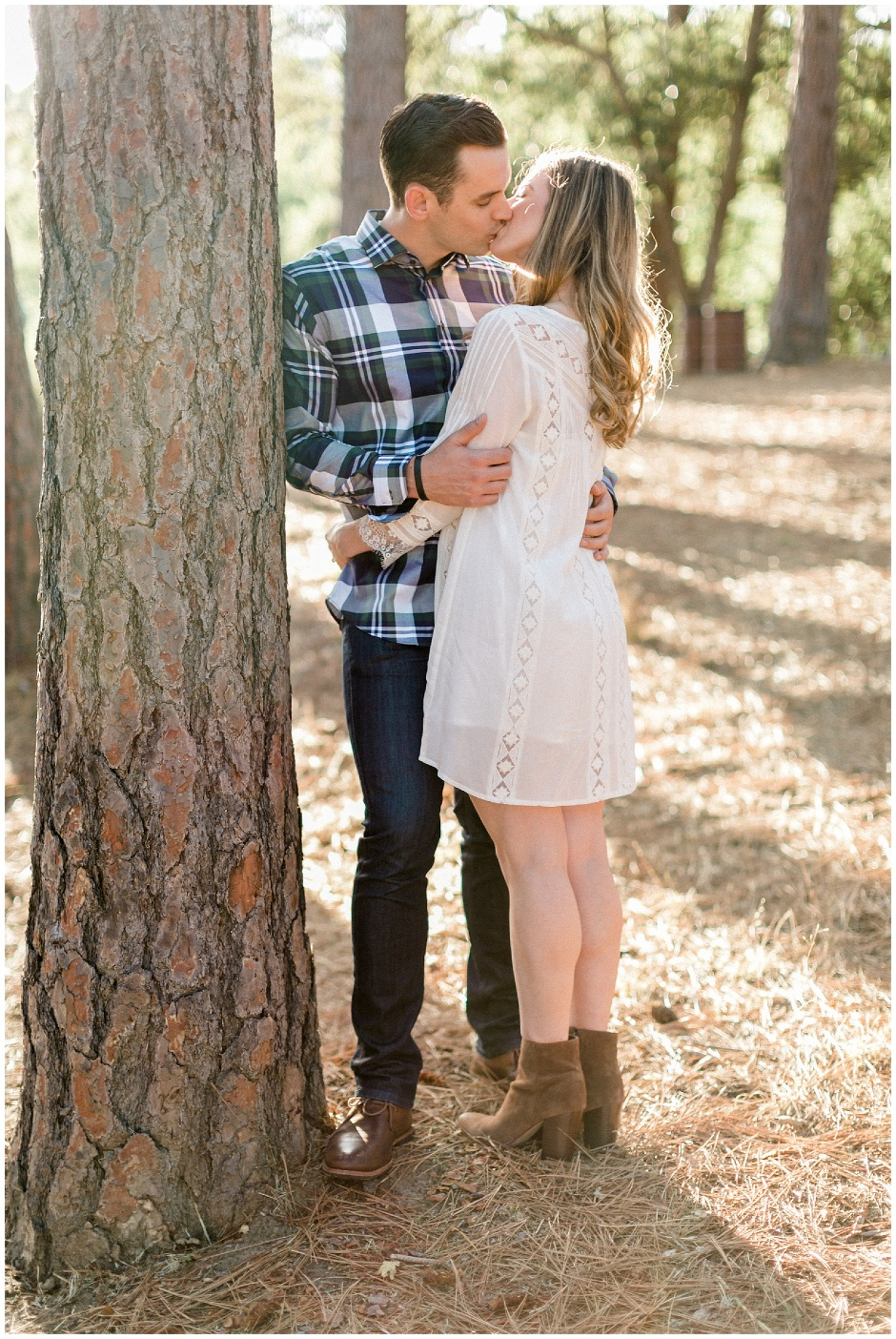 guy leaning against a tree kissing his girl