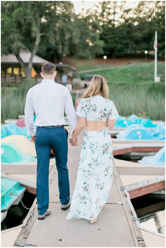 couple walking hand in hand on a boat dock