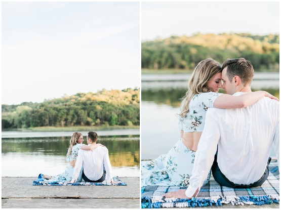 couple sitting on a blanket by a lake