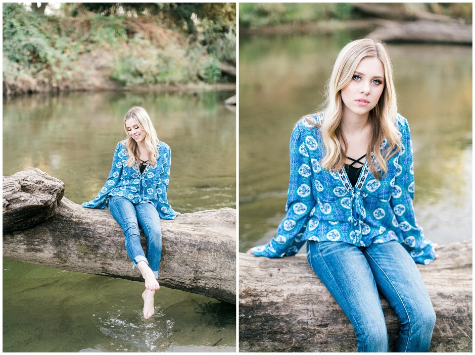 girl in blue shirt and jeans sitting on a log across a river