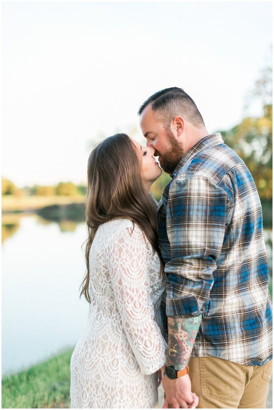 couple kissing in front of a lake
