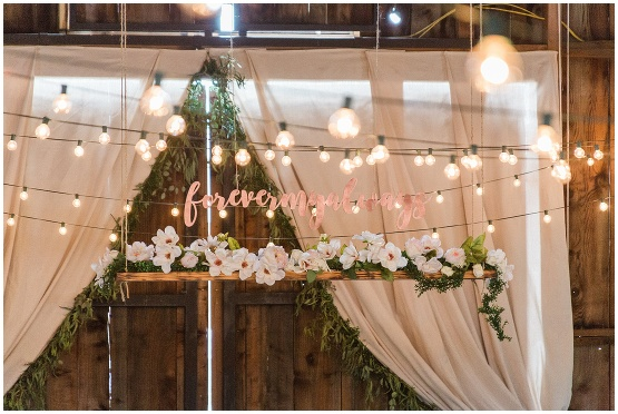 cafe lights and sign above wedding party table