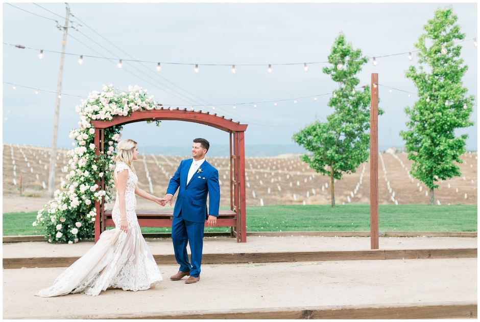 couple walking in front of a rose arbor