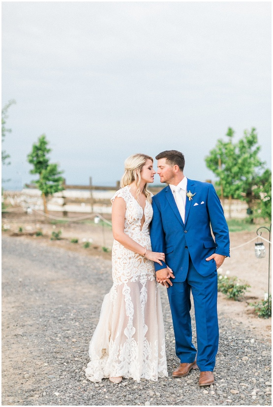 bride in lace dress, groom in blue suit walking down a path