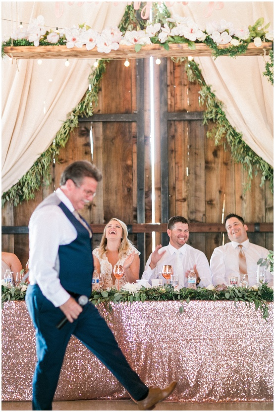 grooms father giving a funny toast, bride and groom laughing