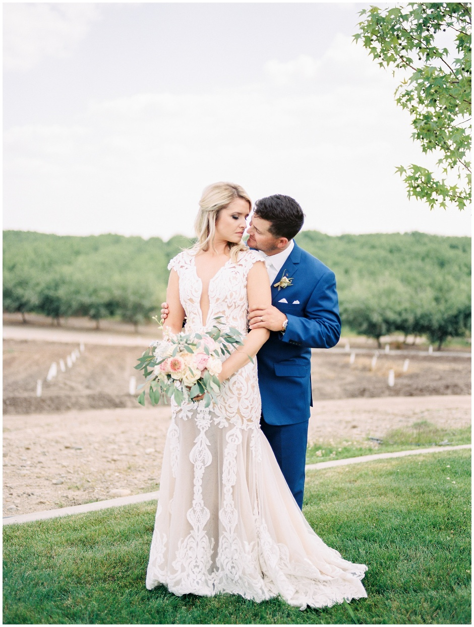 portrait of bride and groom standing on a hillside in front of an orchard
