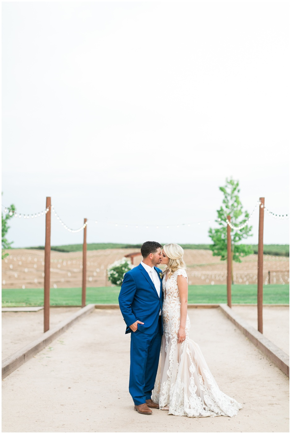 bride and groom kissing on a bocce ball court