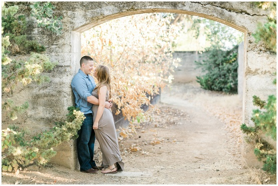 two people leaning against an old stone structure