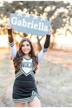cheerleader holding a name sign