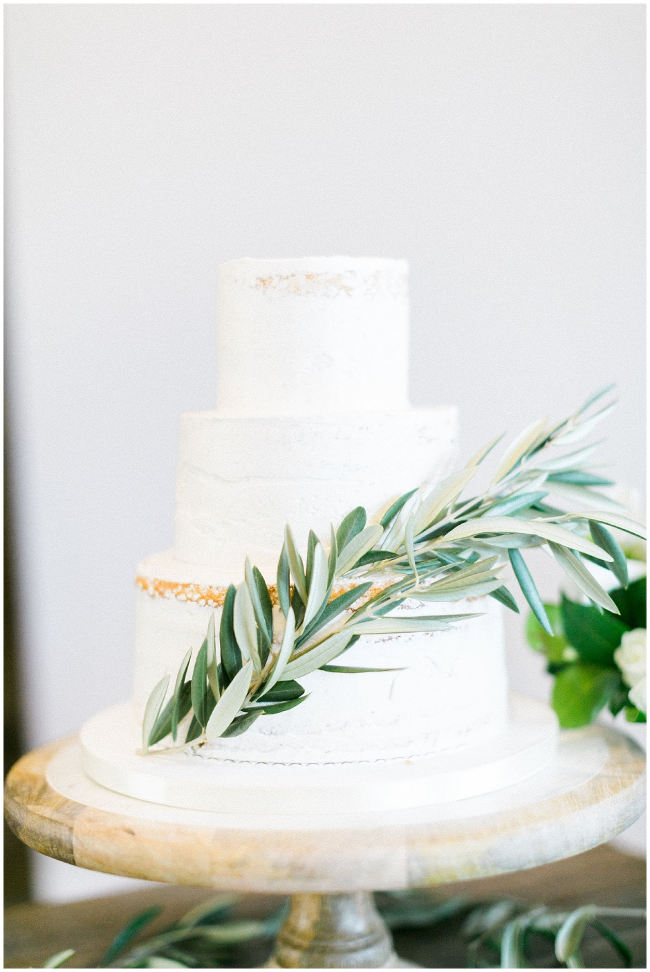 simple white wedding cake with olive branch details