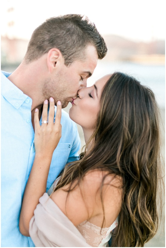 couple kissing with engagement ring showing