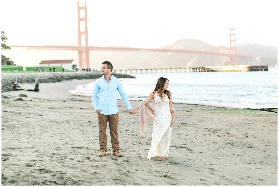 couple holding hands in front of the golden gate bridge