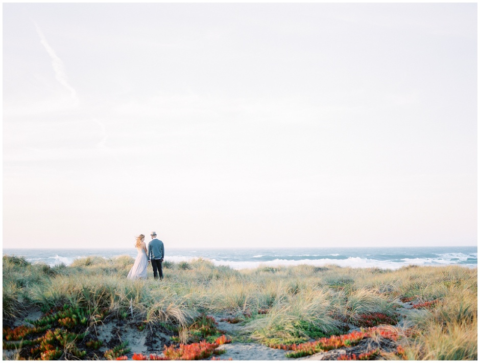 couple standing on a cliff overlooking the seashore