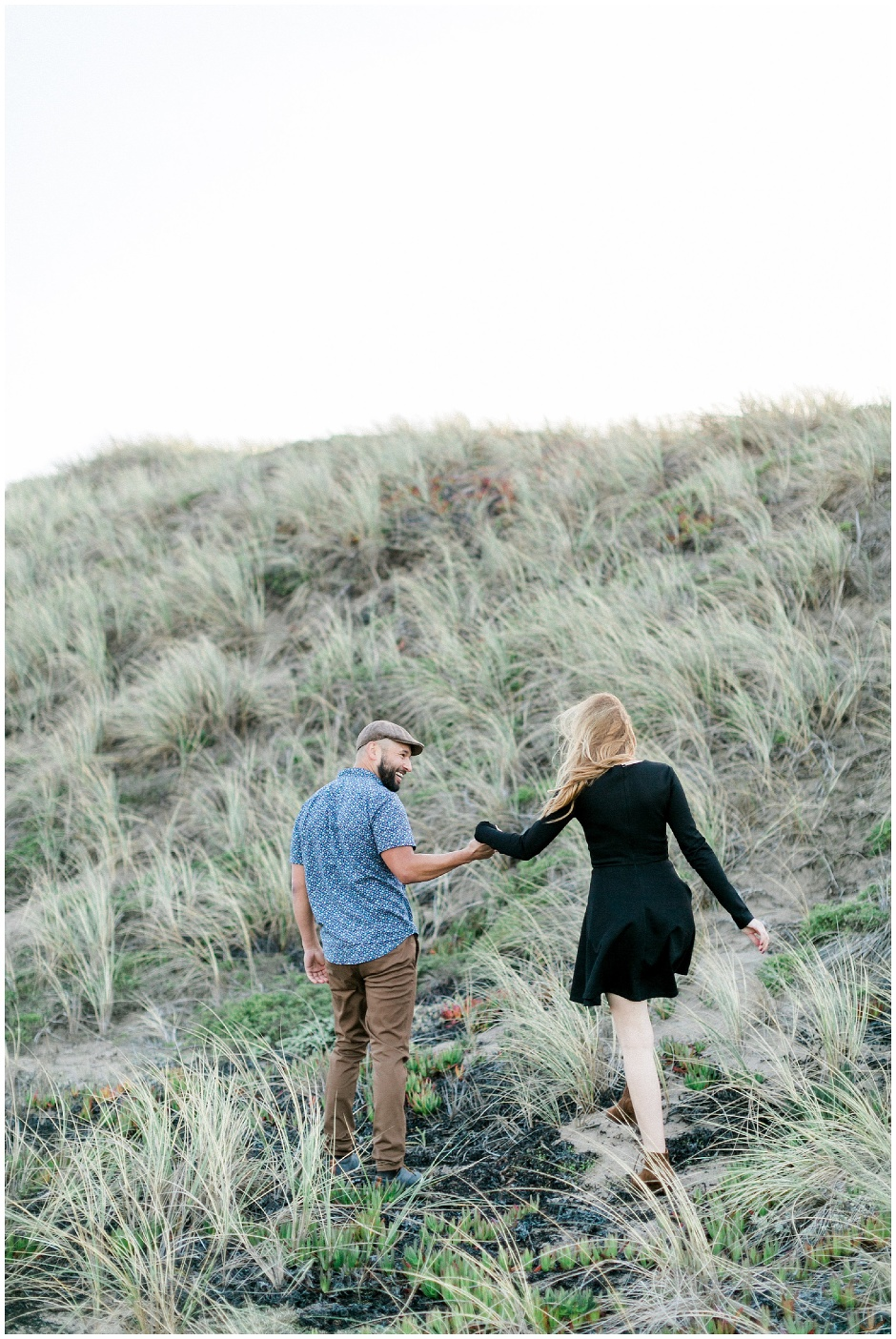 couple walking along seagrass covered hills