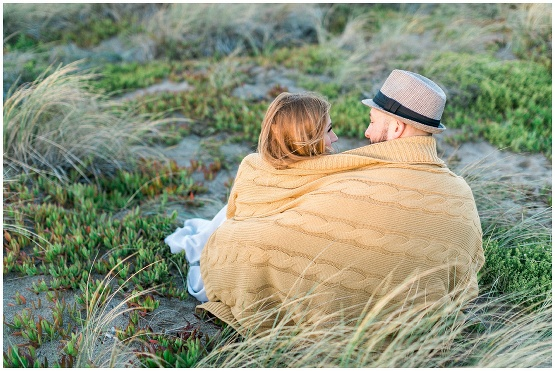 couple wrapped in a yellow blanket by the sea